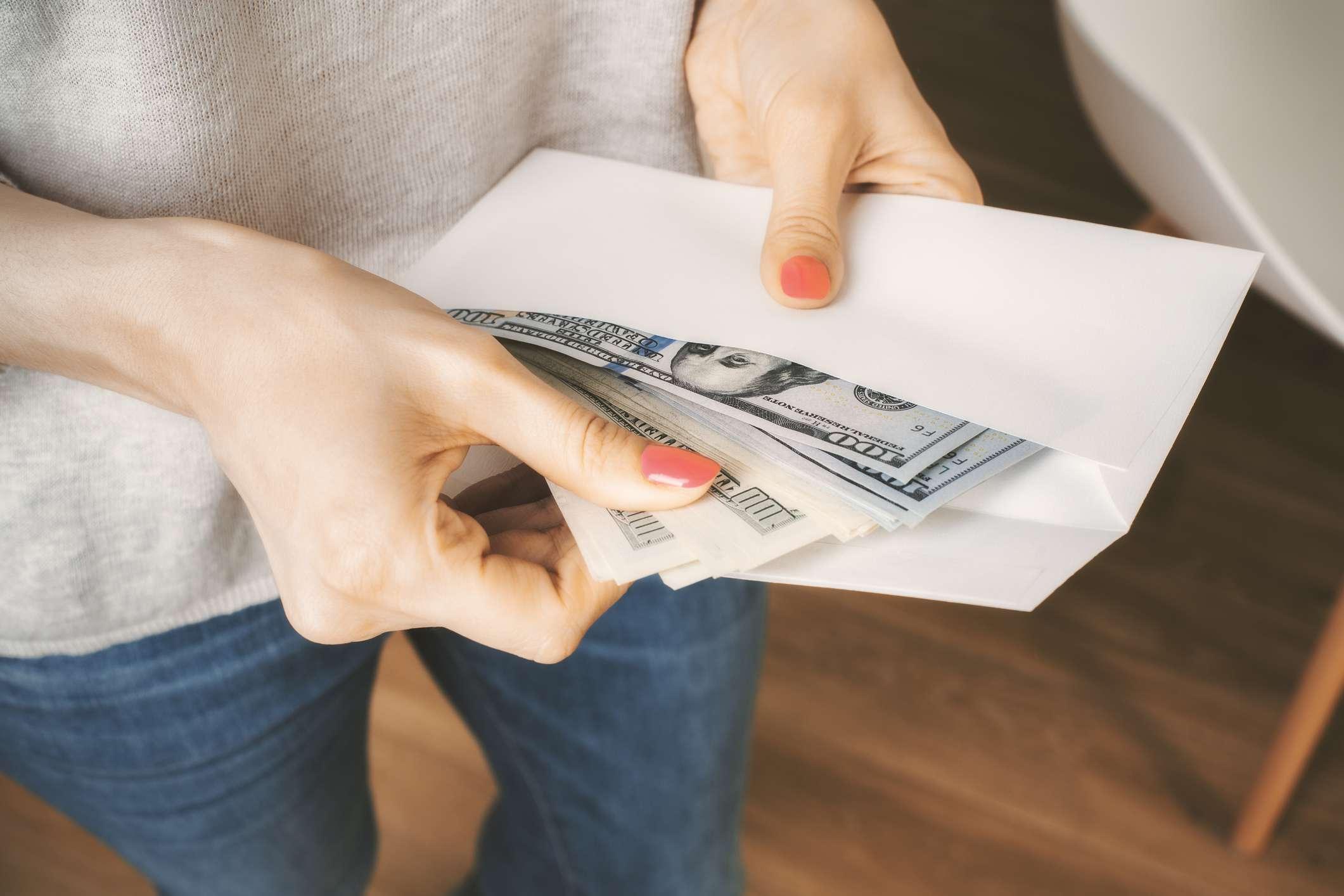 hands holding envelope of money