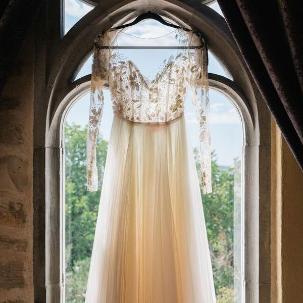 Wedding gown with sheer top hanging in front of window