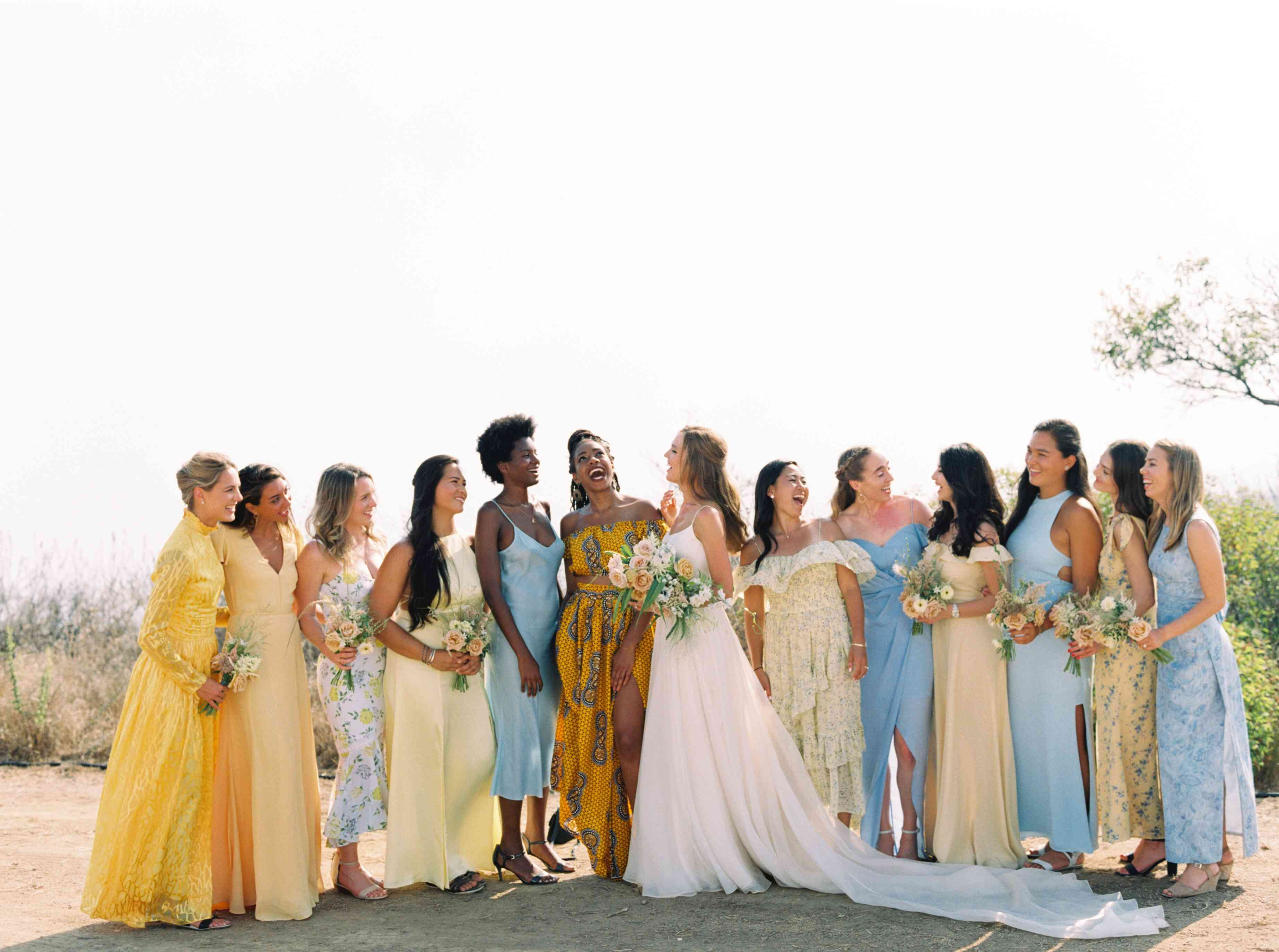 A group of bridesmaids in mismatched dresses standing outdoors with the bride in the middle