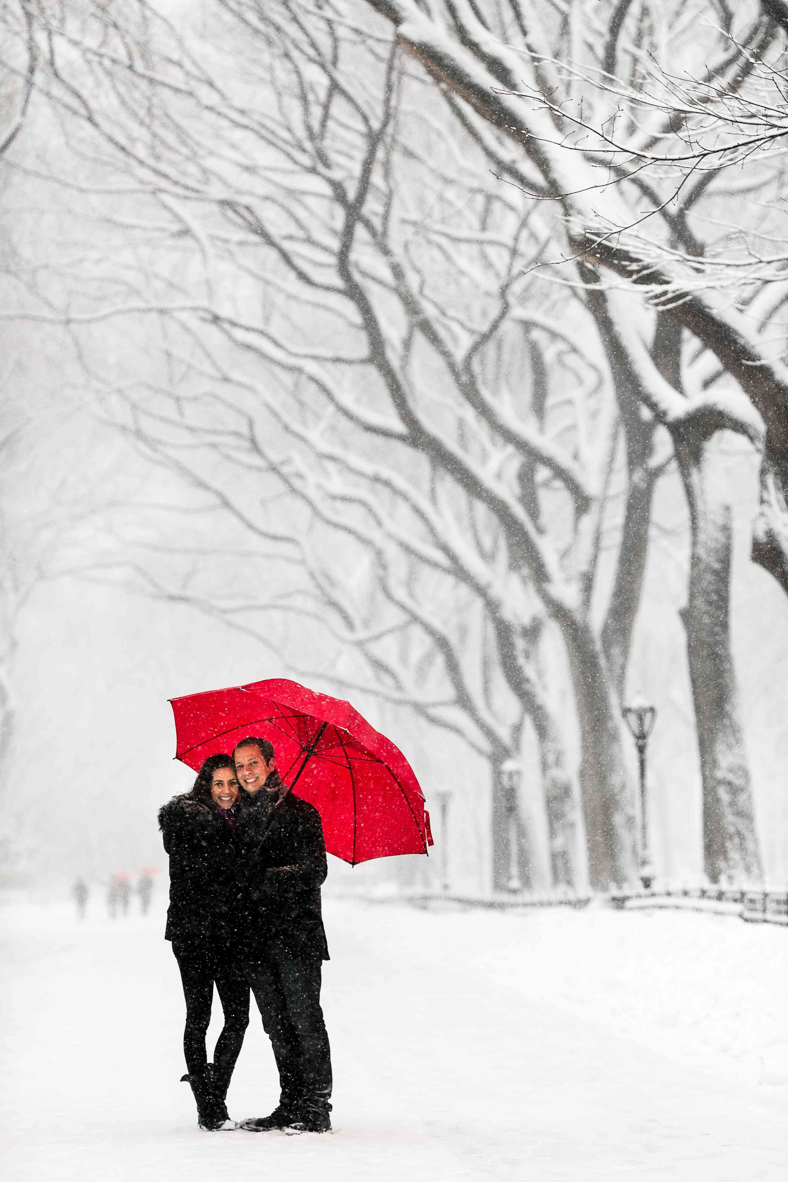 Couple posing in the snow with umbrella