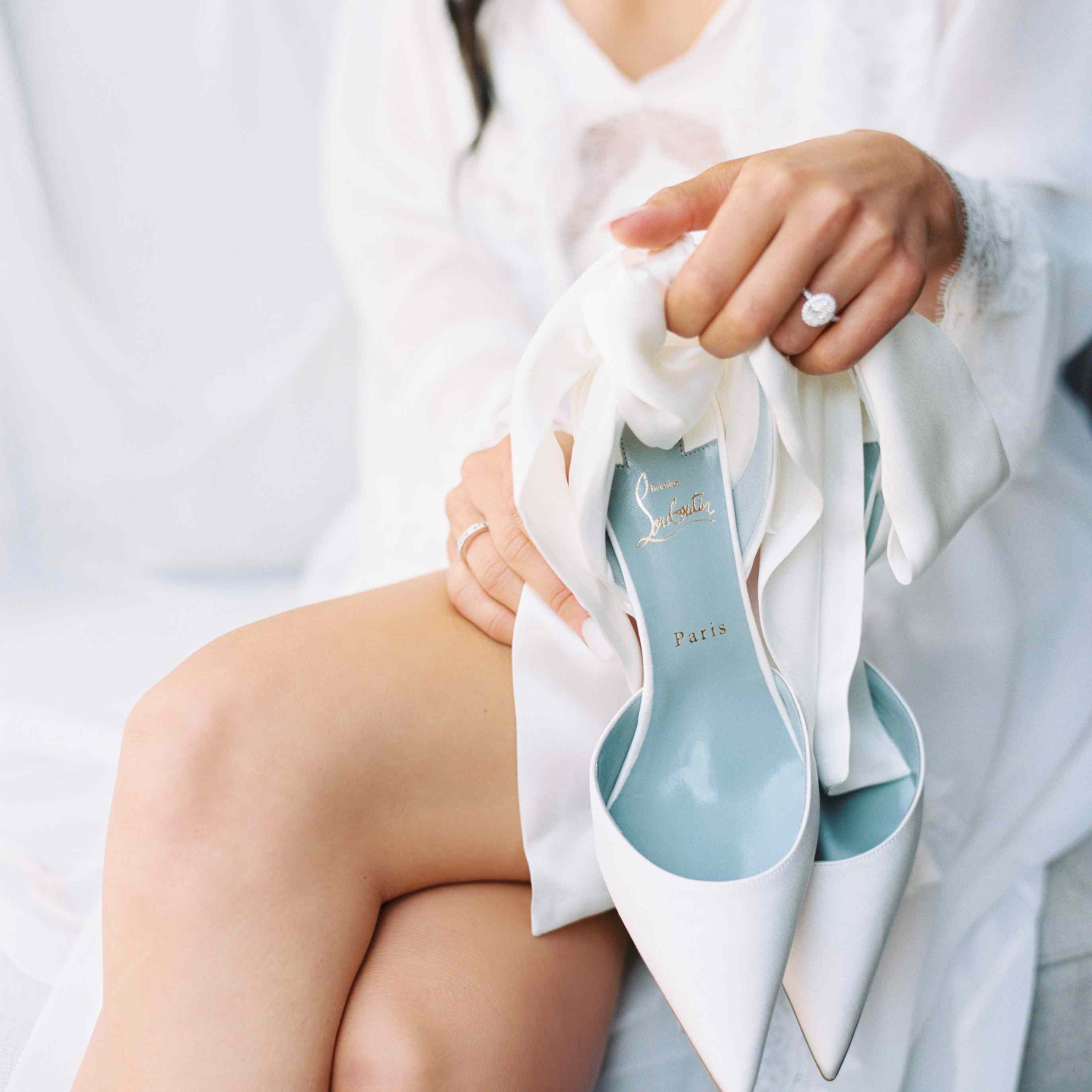 The bride holds her shoes