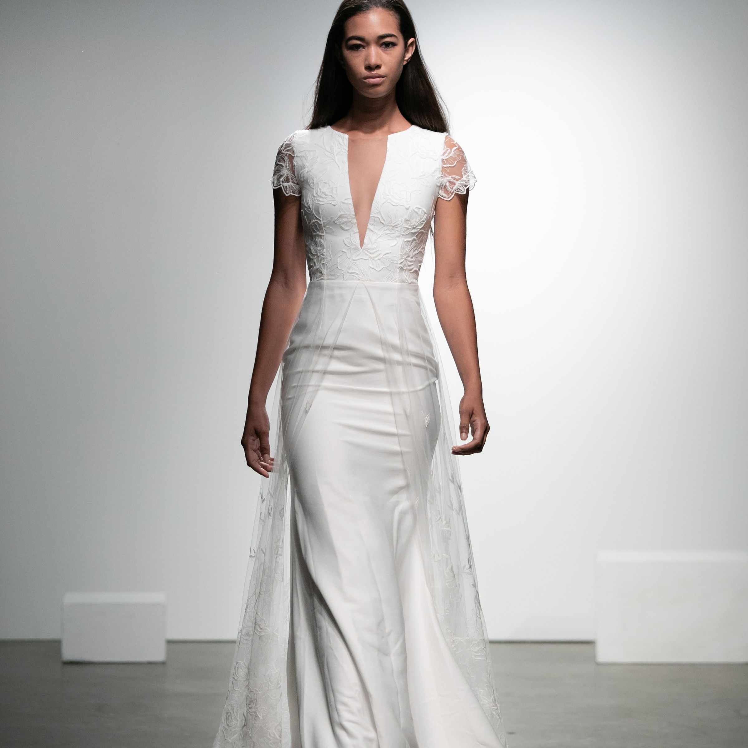 V-neck wedding gown with cap sleeves, plunging illusion neckline, and embroidered tulle overskirt