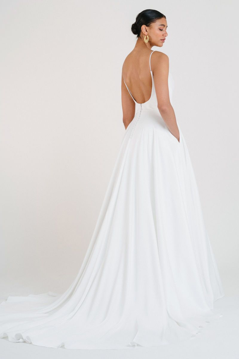 Model in scoop back white wedding gown with pockets