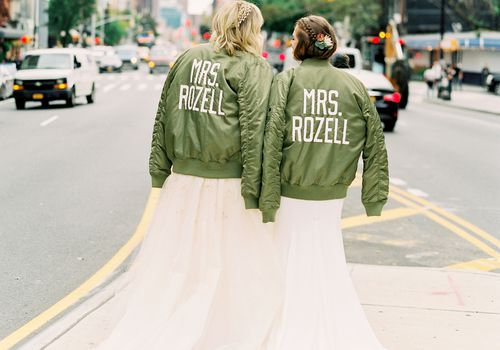 """Two brides standing on the sidewalk in NYC wearing matching green jackets with """"Mrs. Rozell"""" embroidered on the back"""