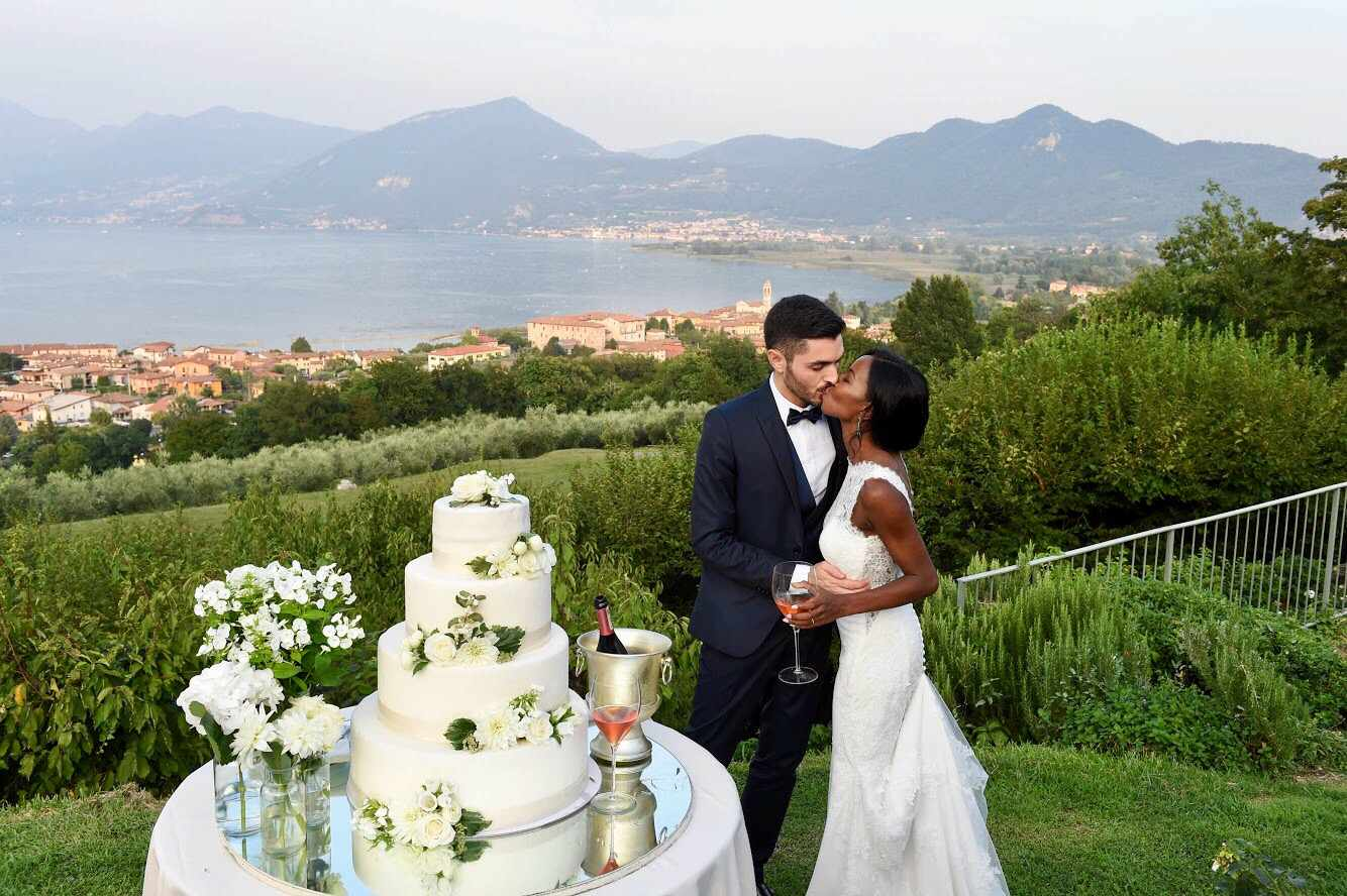 Bride and groom kissing by wedding cake