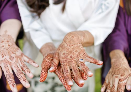 Bride with henna on her hands wearing an engagement ring