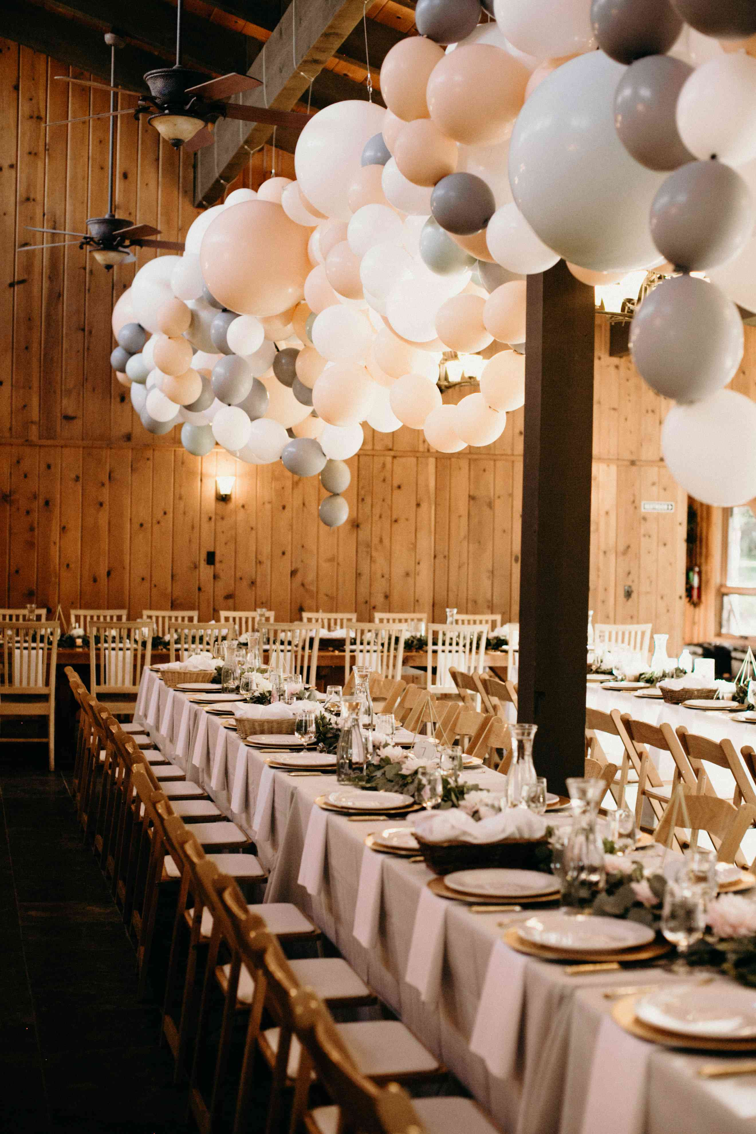 A large hanging balloon installation in neutral colors hanging over reception tables