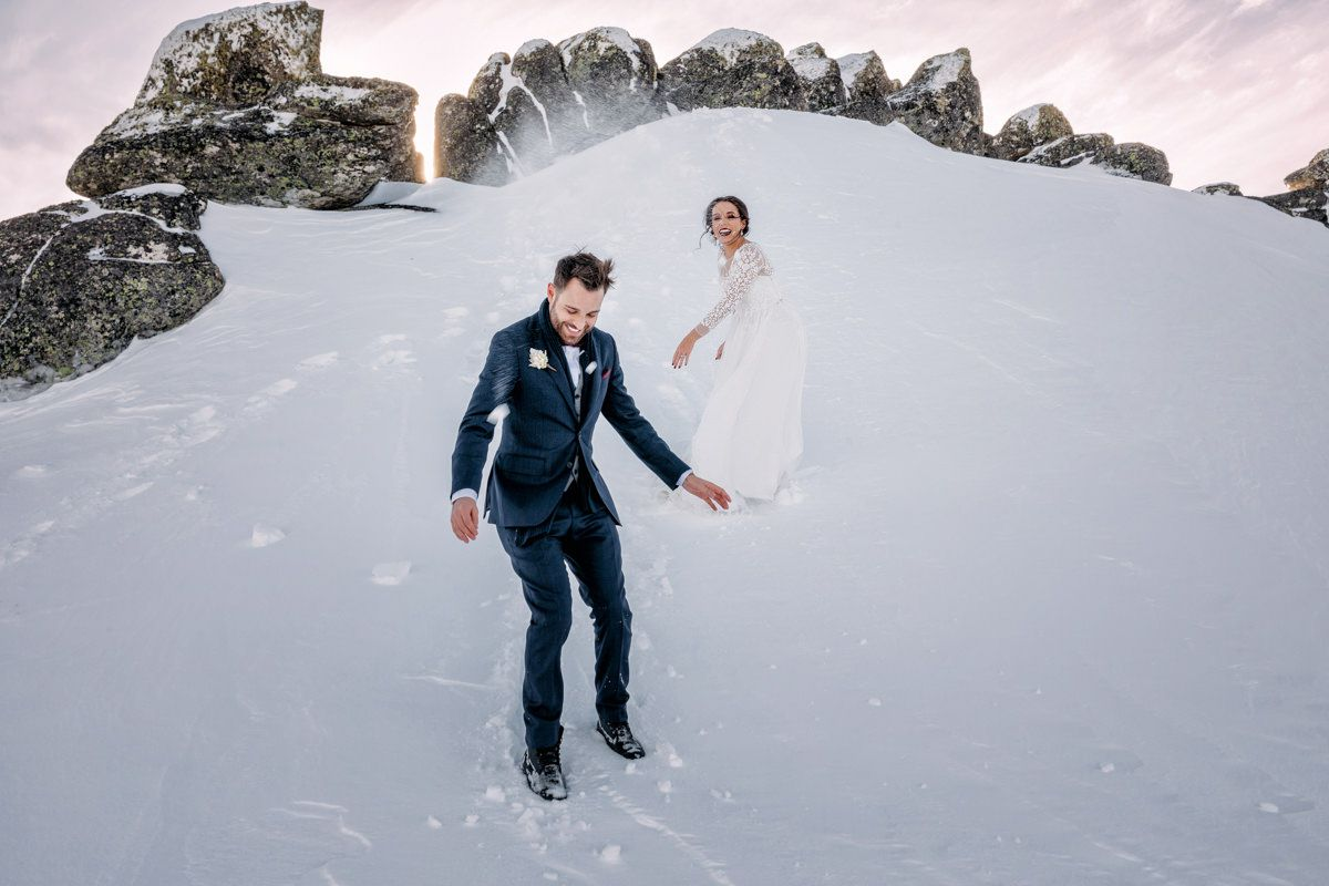 Bride and groom having a snowball fight