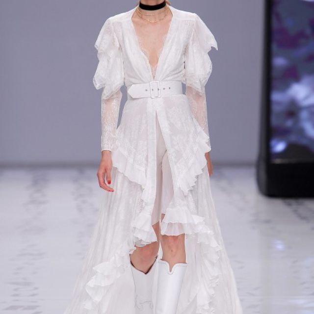 Model in a chiffon dress embroidered with georgette ruffles and sleeves finished with chantilly lace featuring a deep V neckline, a wide belt, and an asymmetrical high-low skirt
