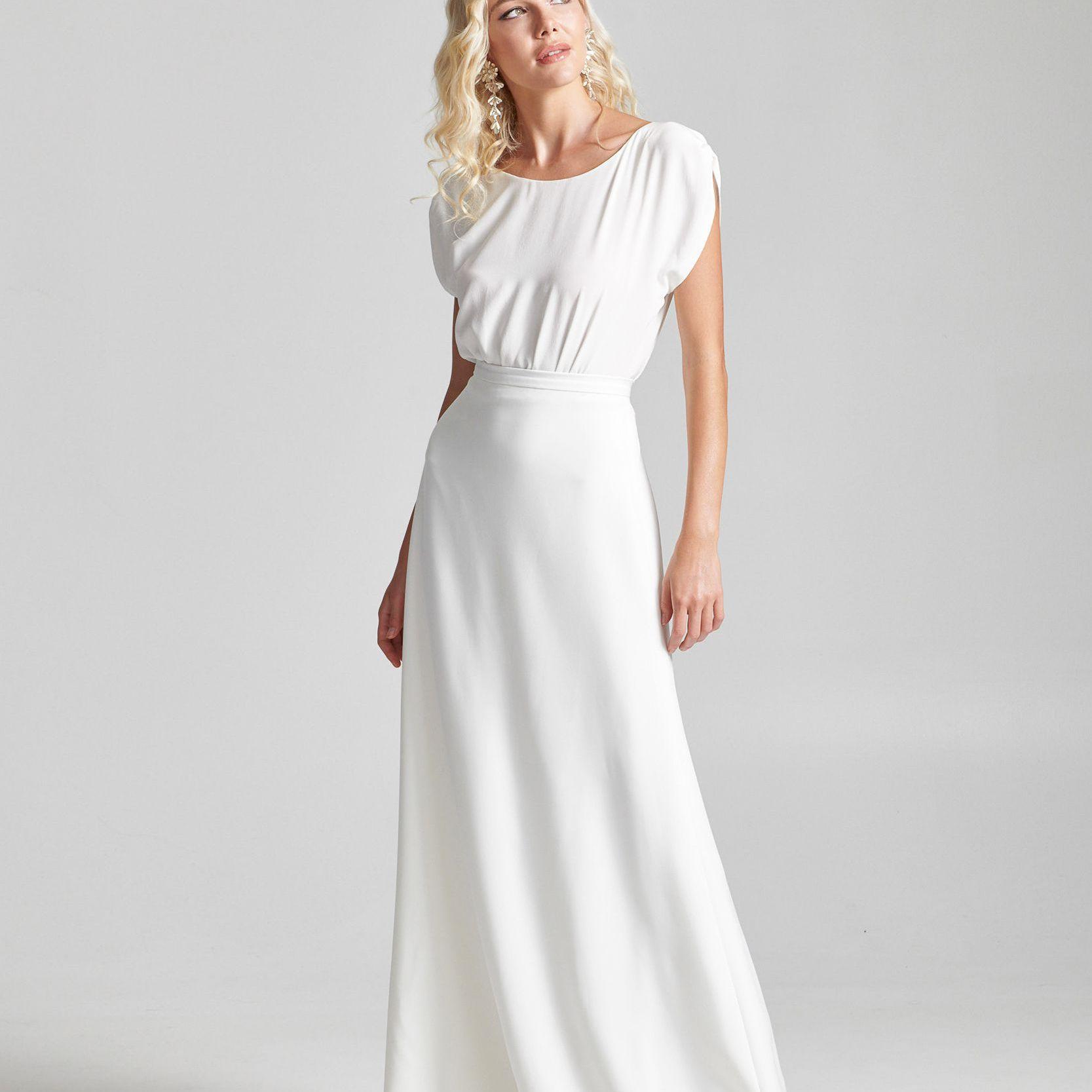 Model in short-sleeve top with floor length skirt
