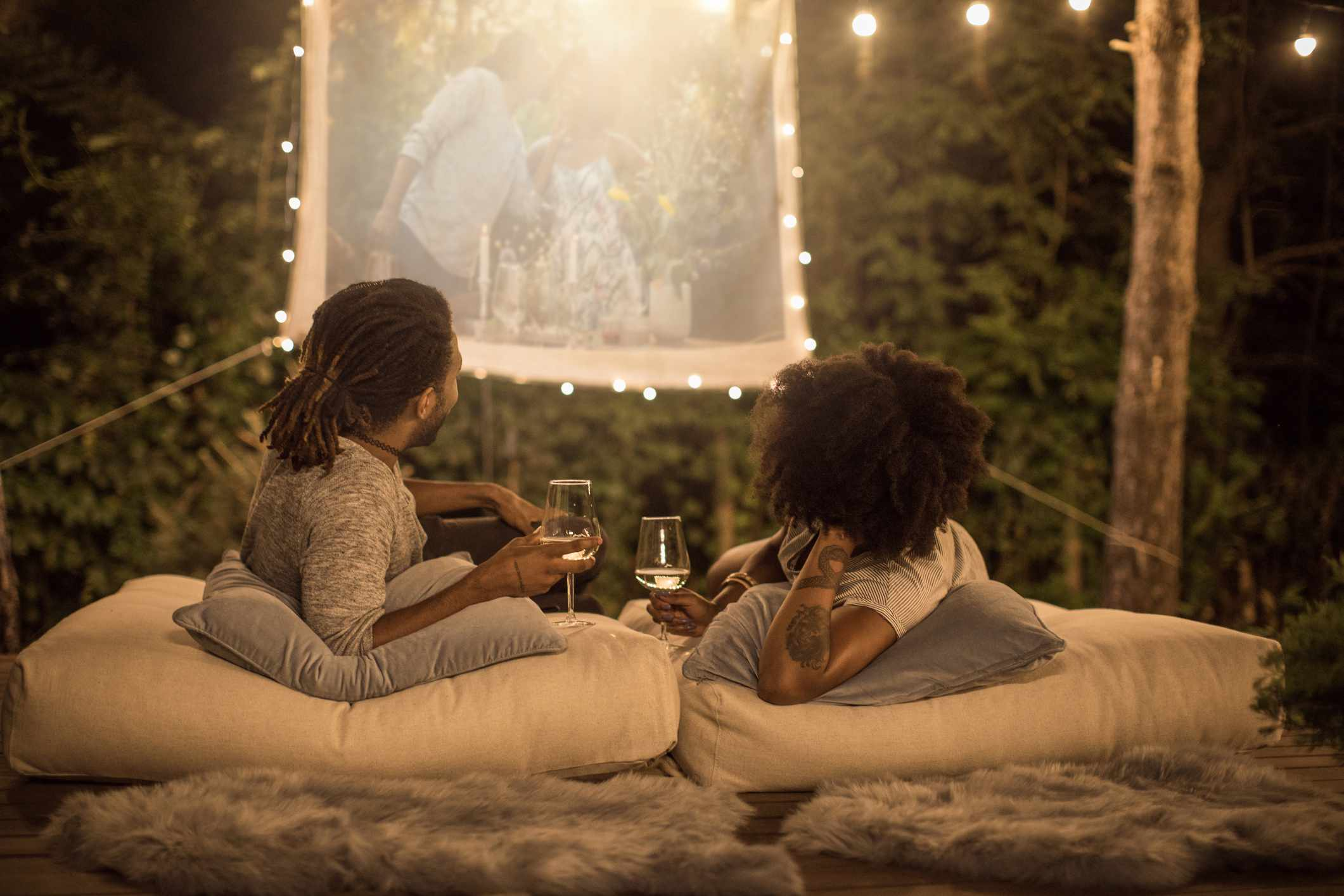 Couple drinking wine and watching a video outside on a projector