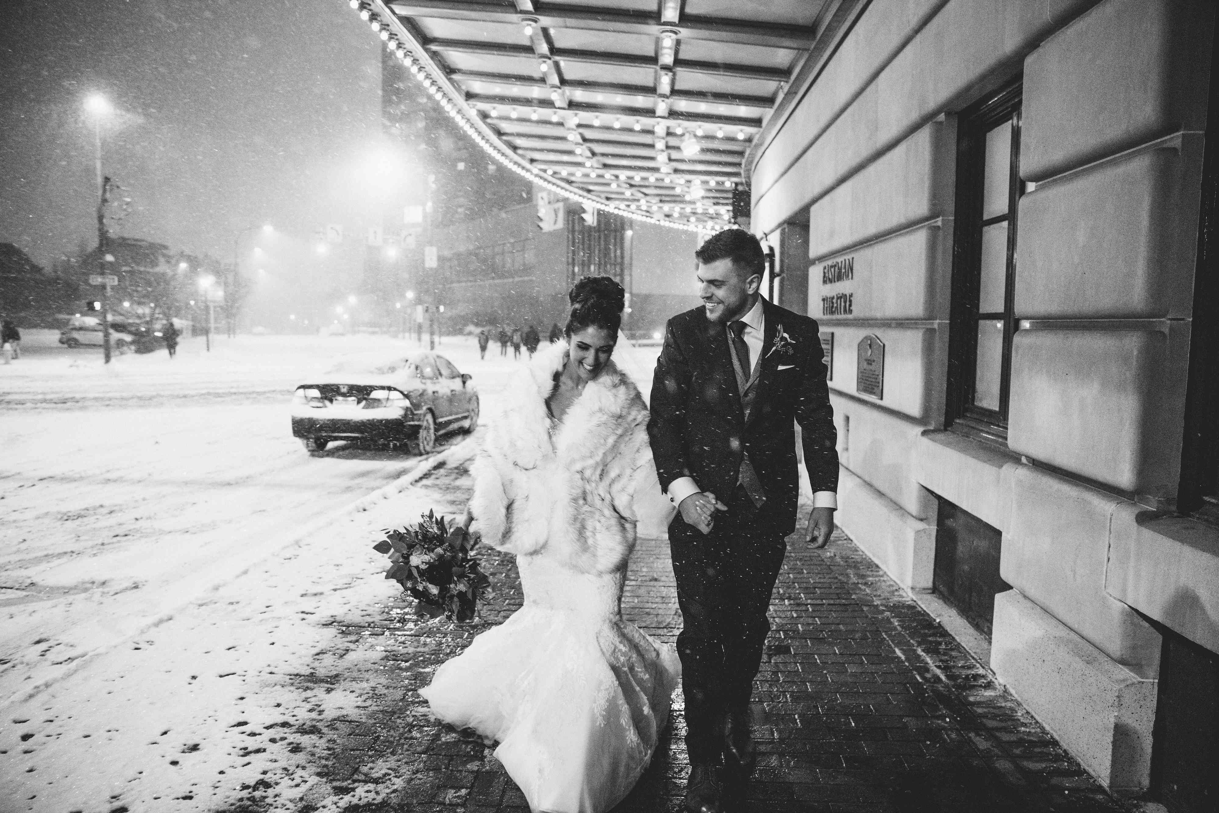 Bride and groom walking through the city while it snows