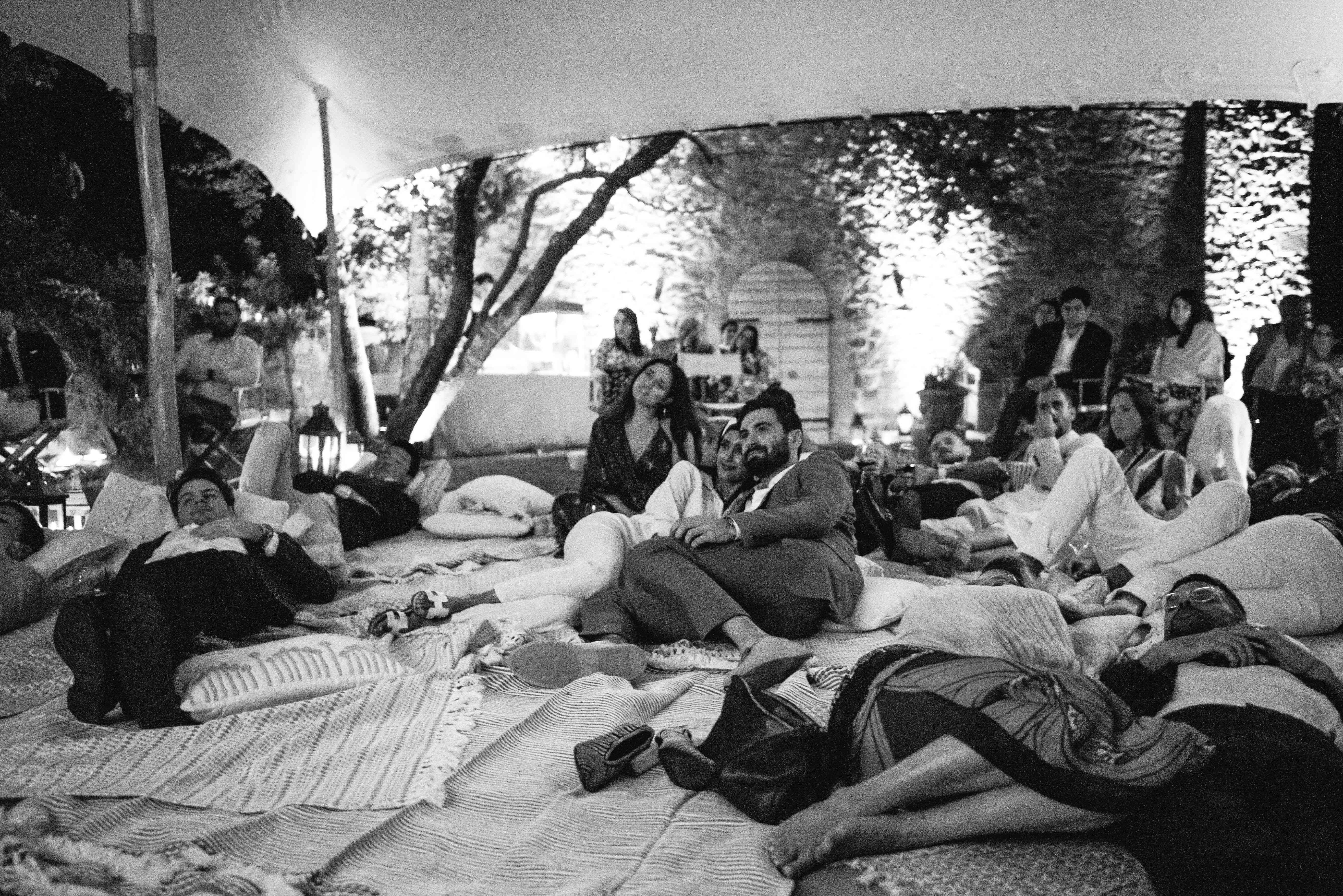 Guests sitting on blankets outdoors under a tent