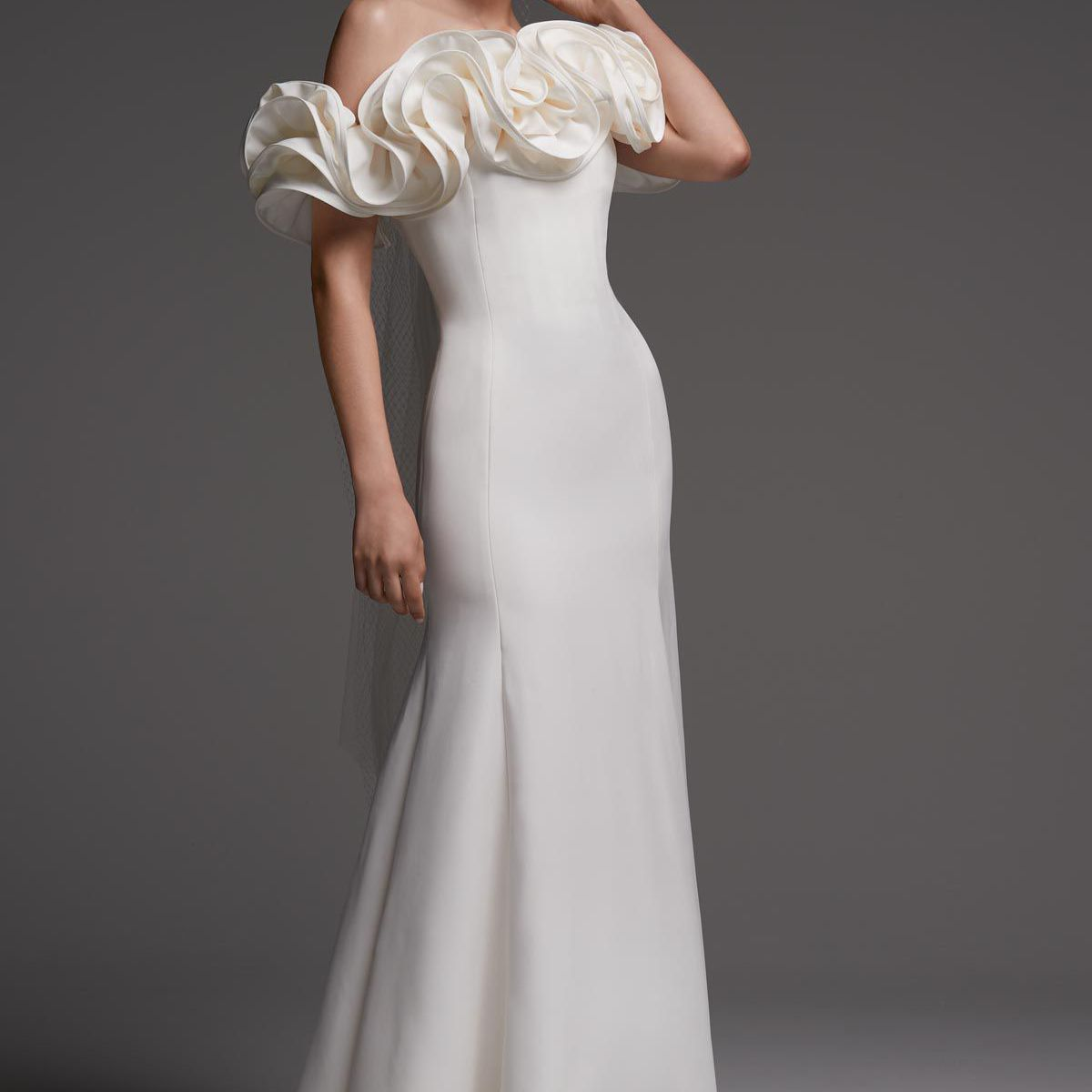 Model in sheath gown with oversized off-the-shoulder interlacing ruffles