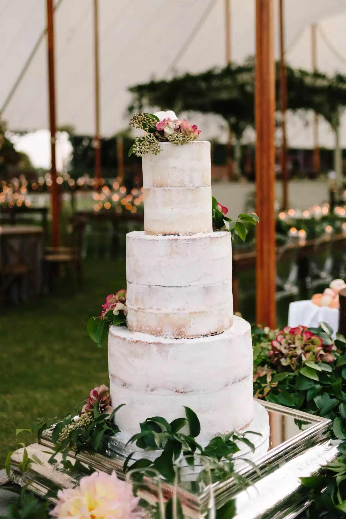 tall semi-naked wedding cake on mirror