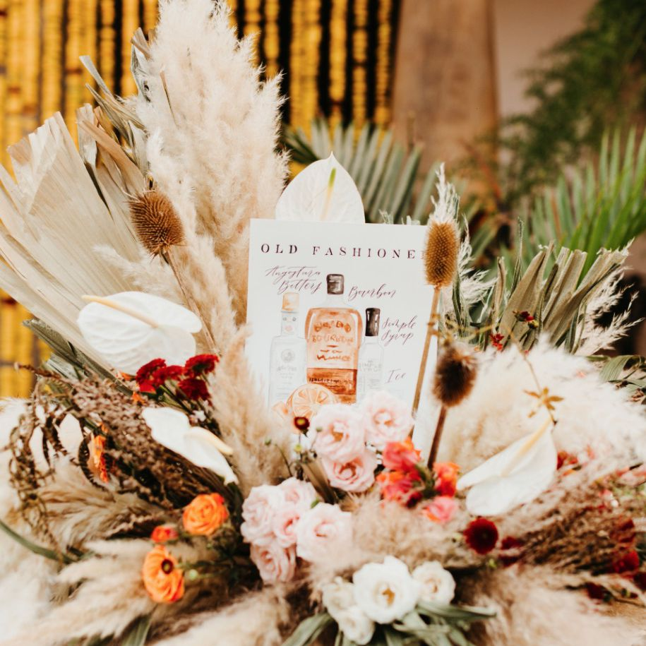 Centerpiece arrangement of dried palms, pampas grass, anthuriums, and flowers
