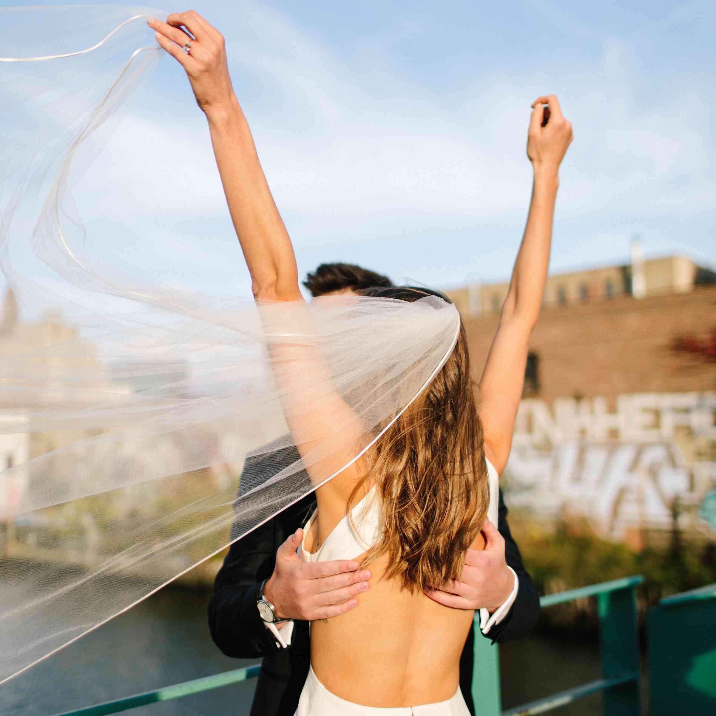 Bride holding veil in wind