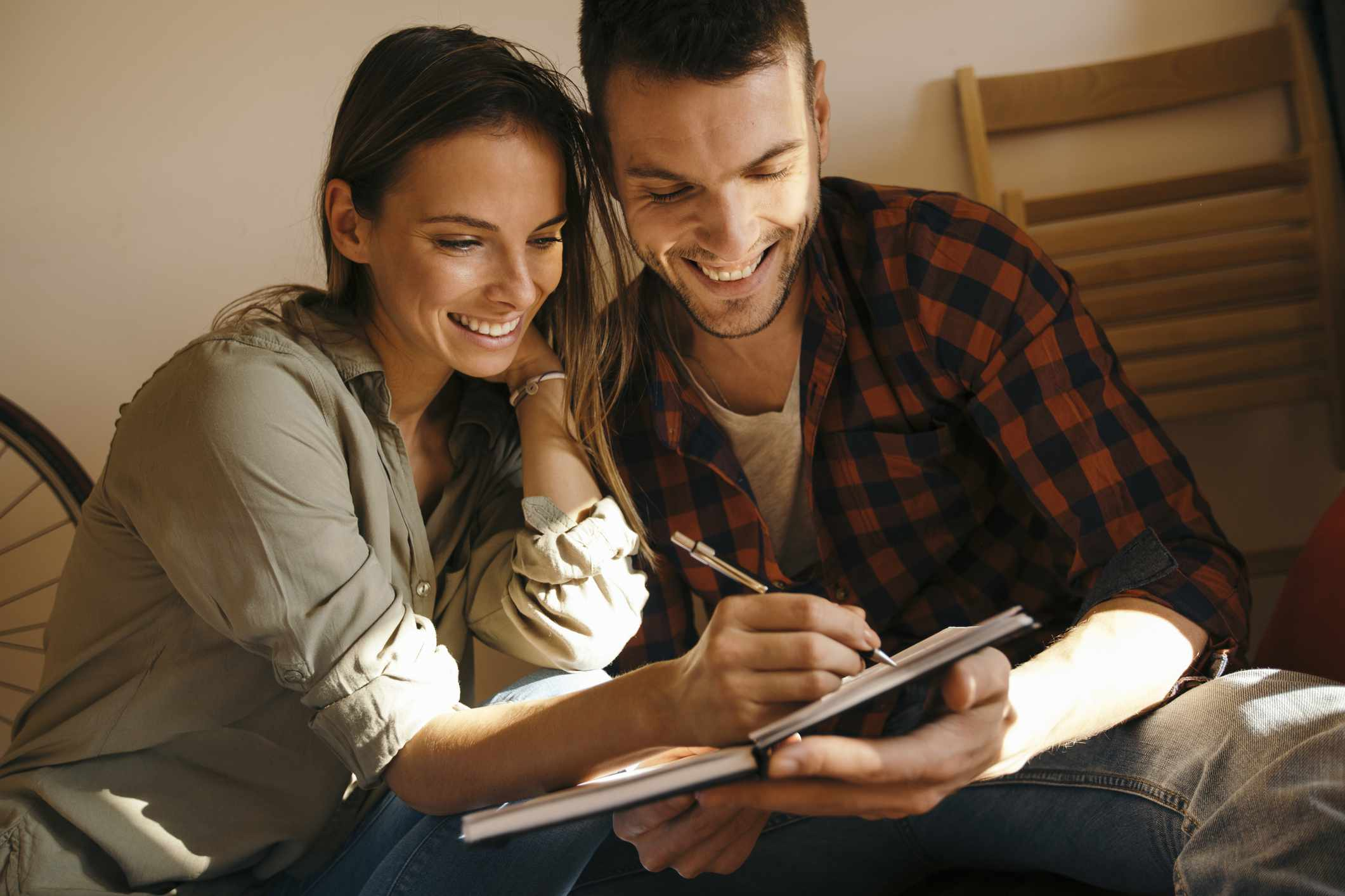 Young couple making a list of plans in a notebook