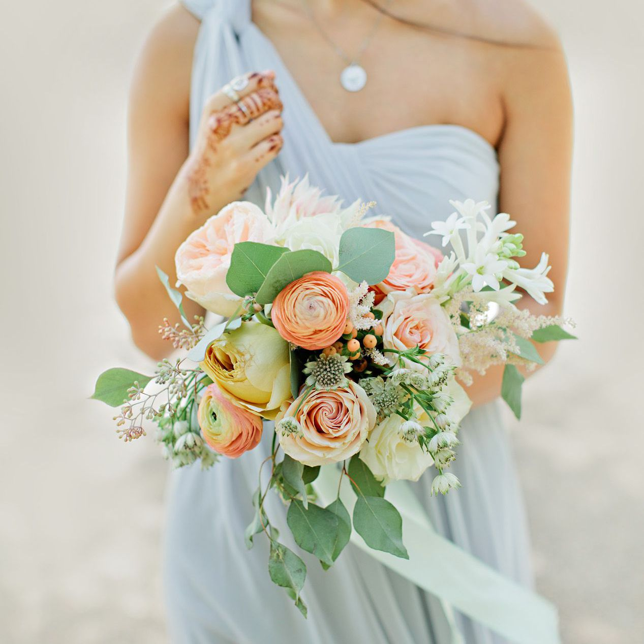 Bride holding a bouquet with pink and orange flowers