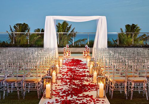 Beachside wedding aisle lined with candles and scattered rose petals