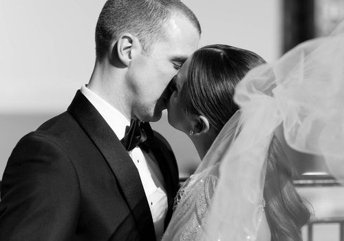 Close-up of bride and groom kissing, black and white