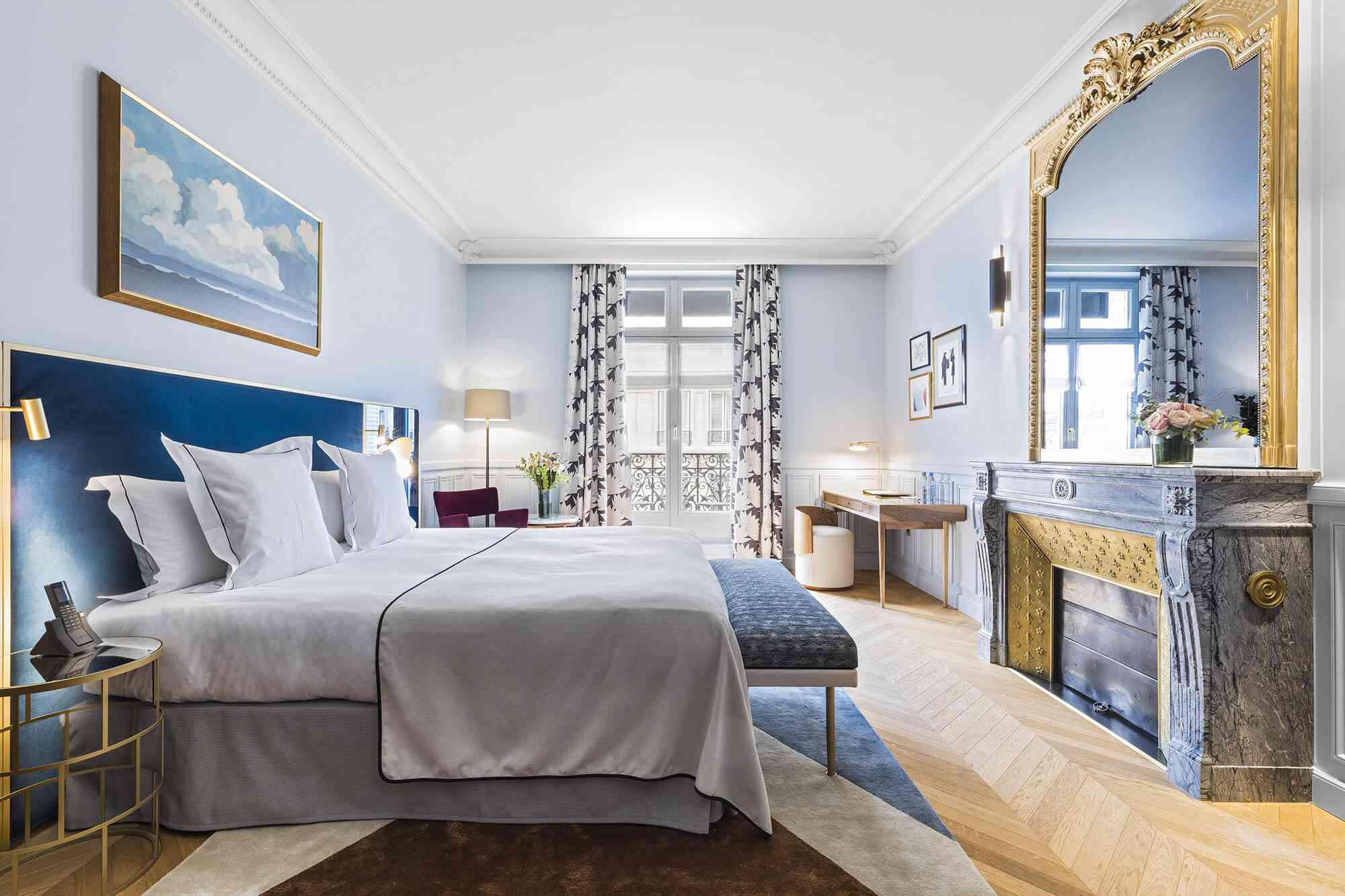 Hotel bed on a blue headboard across from a large gilded mirror on vanity, in front of patio doors on back wall