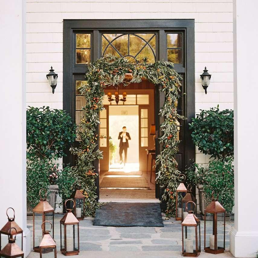Wedding entrance with lanterns, garland, and greenery