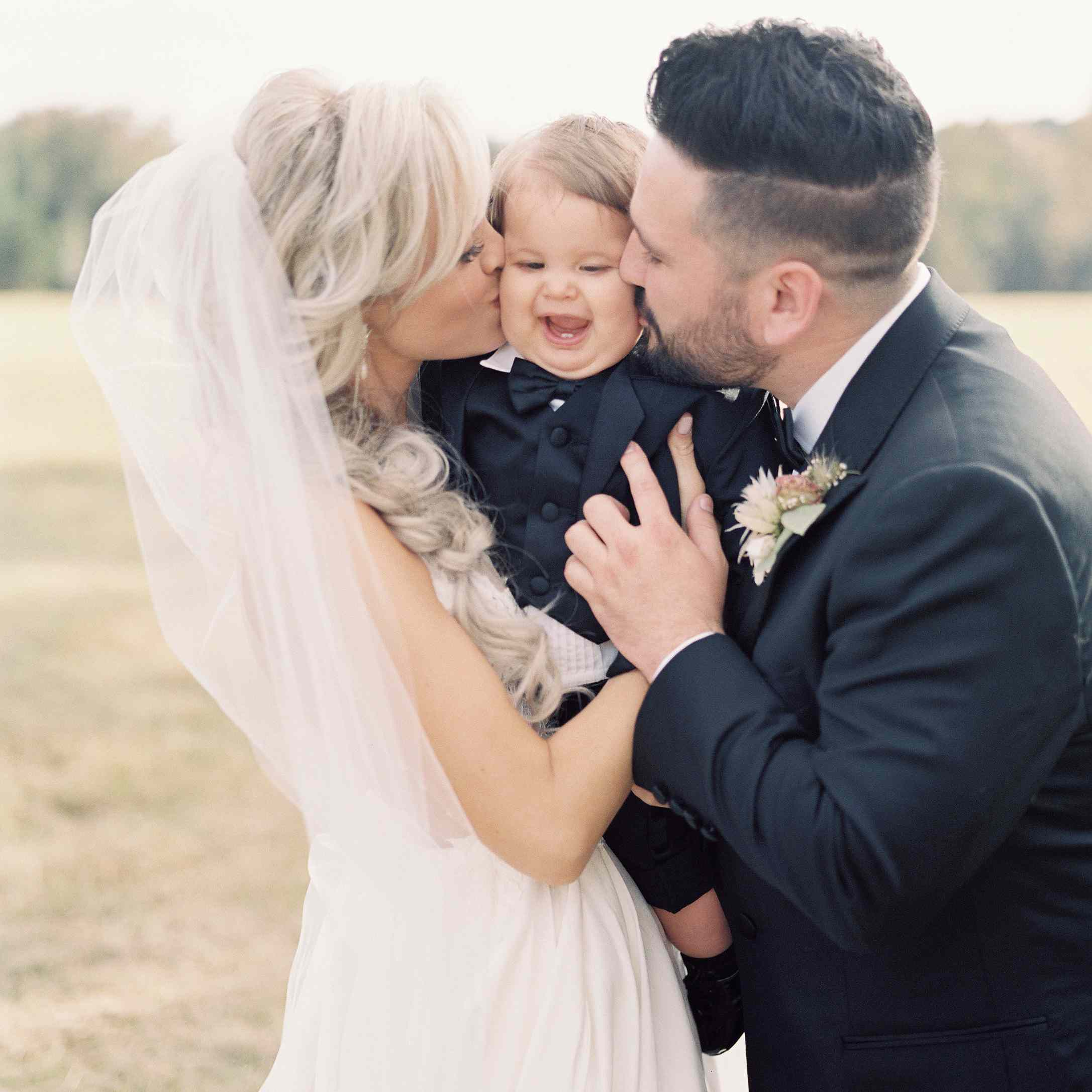 <p>Bride and groom kissing baby</p><br><br>