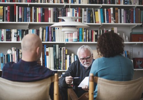 Senior therapist explaining analysis to mature couple against bookshelf at home office