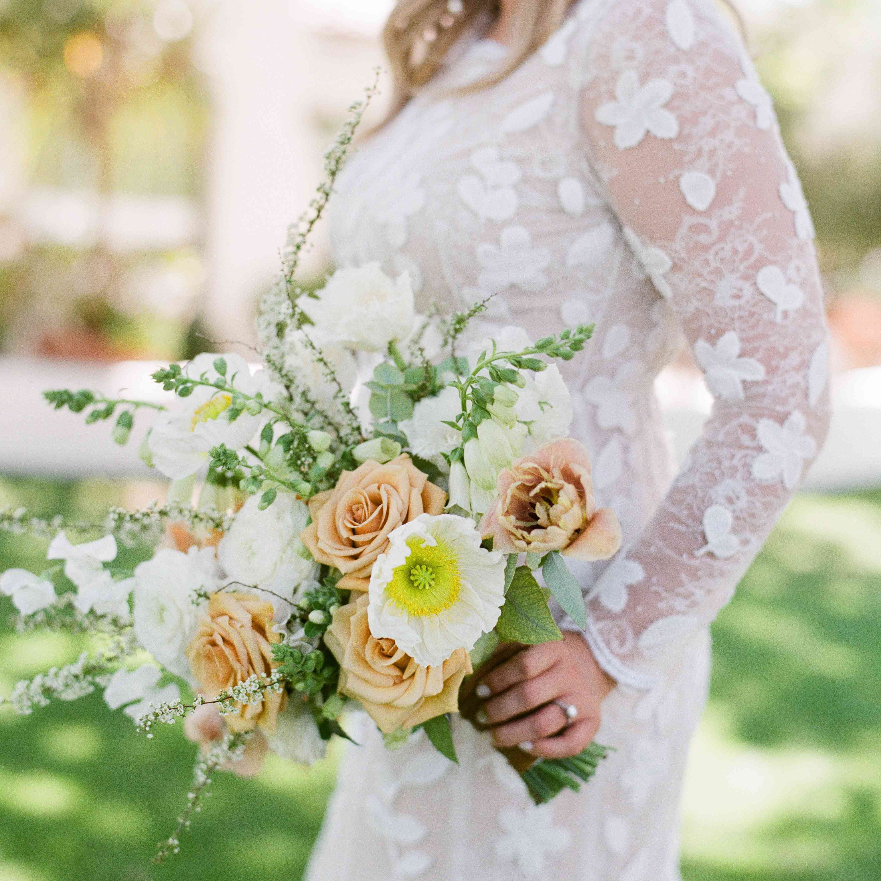 Bride outside holding a bouquet with white and peach flowers