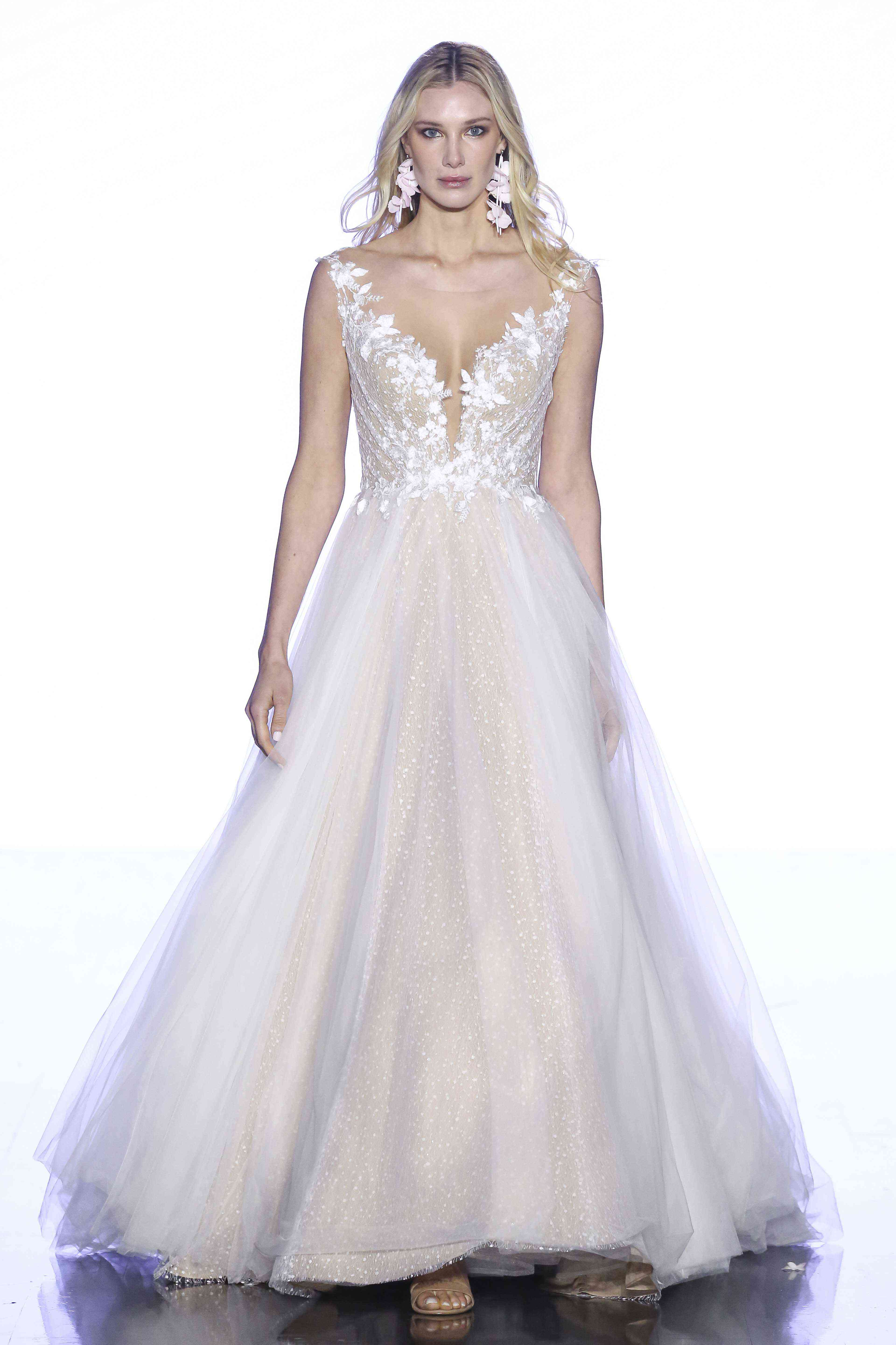 Model in A-line wedding gown with a floral lace bodice and a dotted mesh and tulle skirt