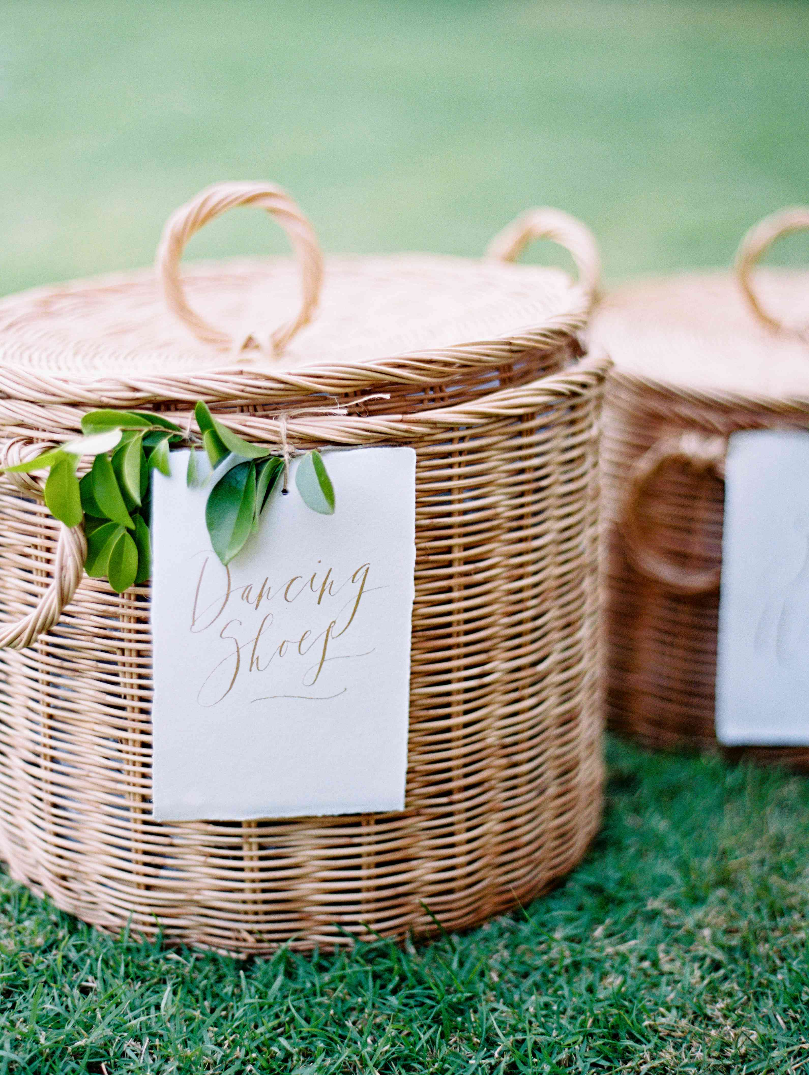 Wicker baskets decorated with greenery with a sign that says
