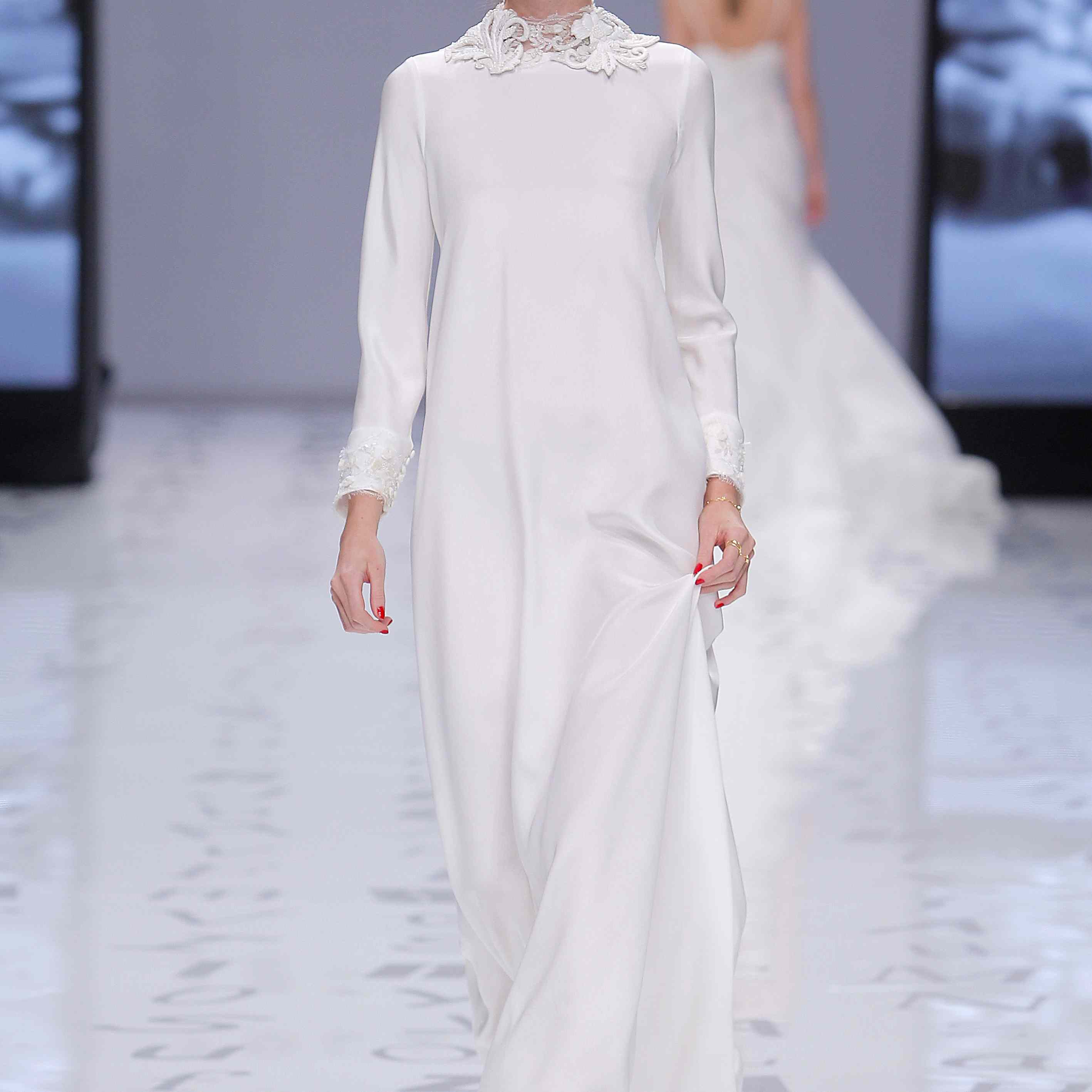 Model in a long-sleeve loose-fitting crepe column dress with a floral-embroidered high neckline and sleeve cuffs