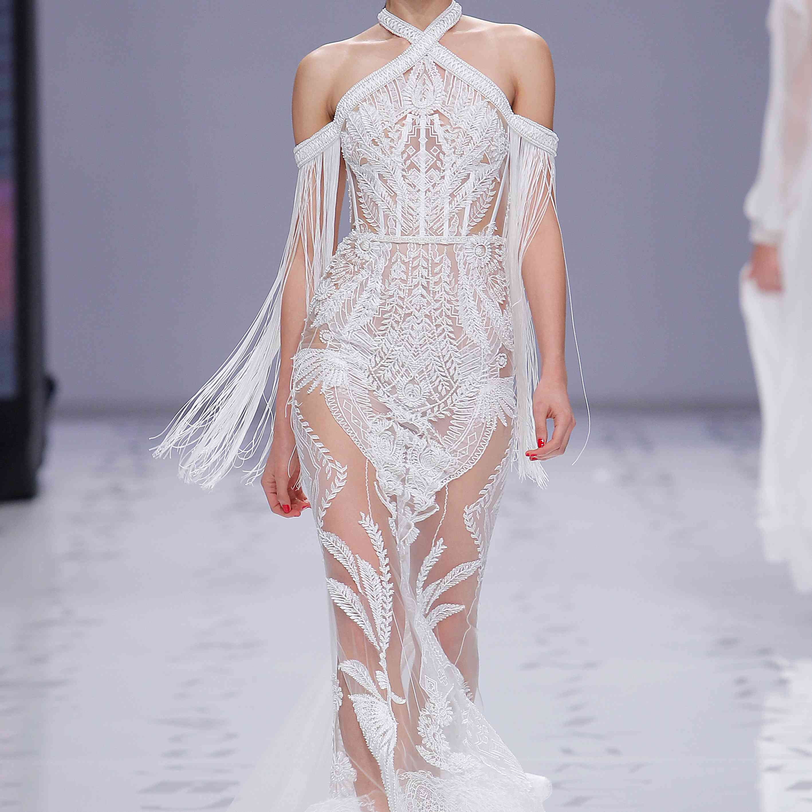 Model in a lace-embroidered sheer tulle mermaid gown with a halter neckline and off-the-shoulder fringe sleeves