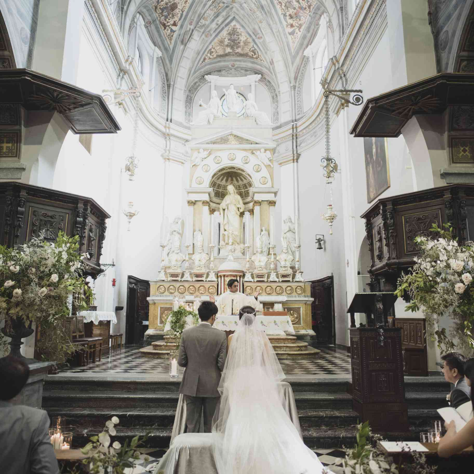 Newlyweds in Catholic Nuptial Mass in front of altar
