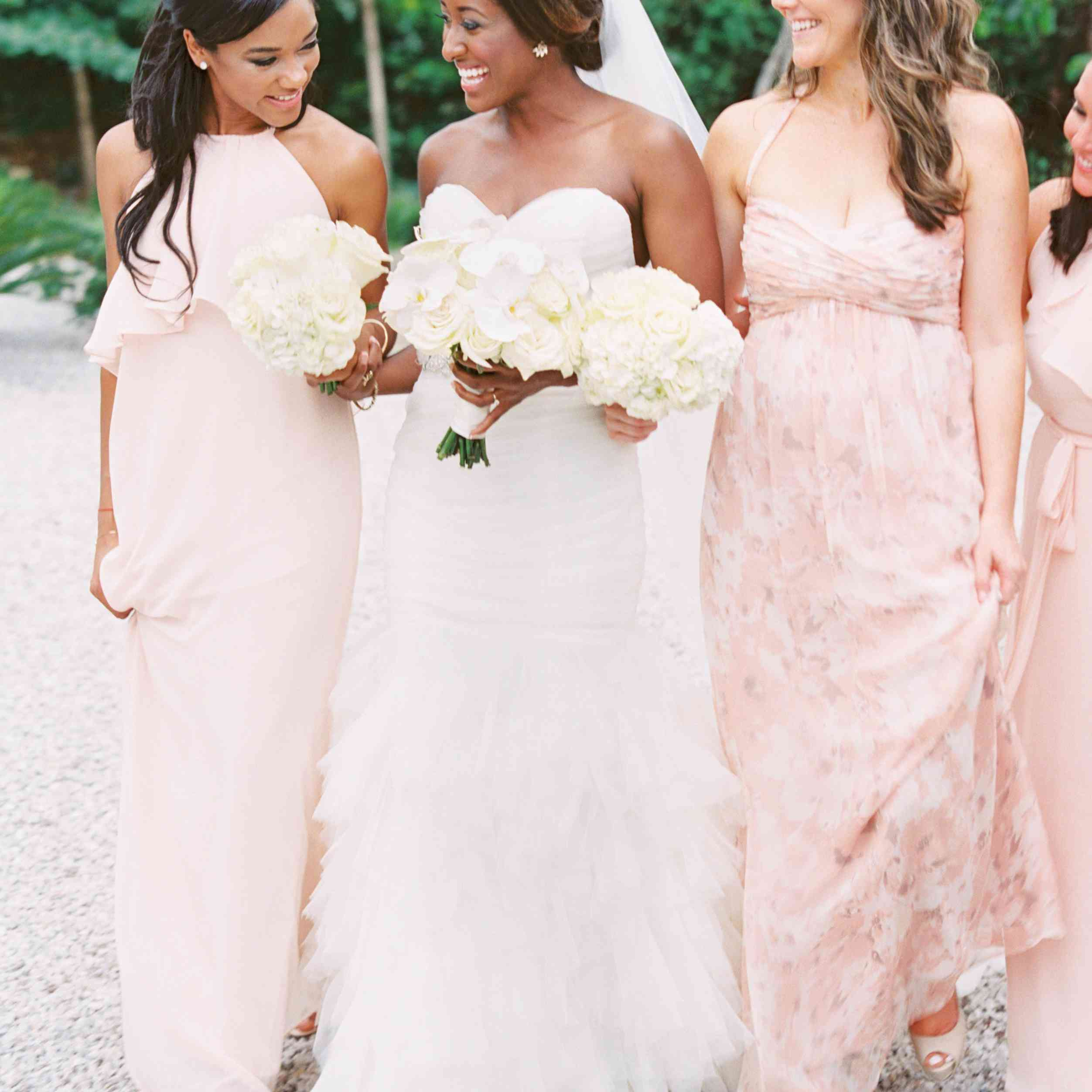 Bridesmaids in pink walking with bride