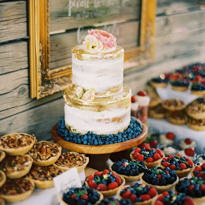 Naked wedding cake with gold details on a table with berry desserts