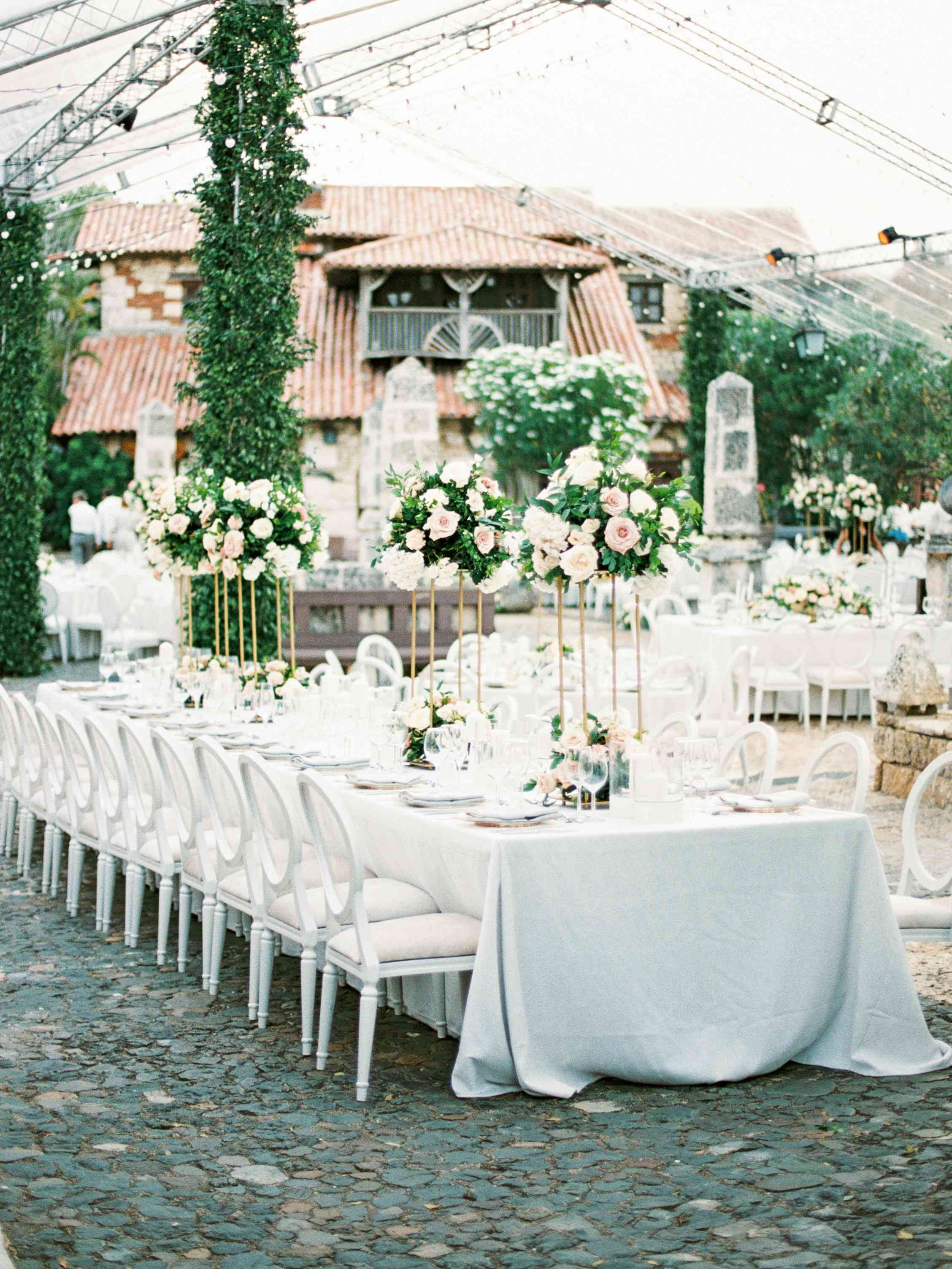 wedding reception decor white tables and elevated floral arrangements