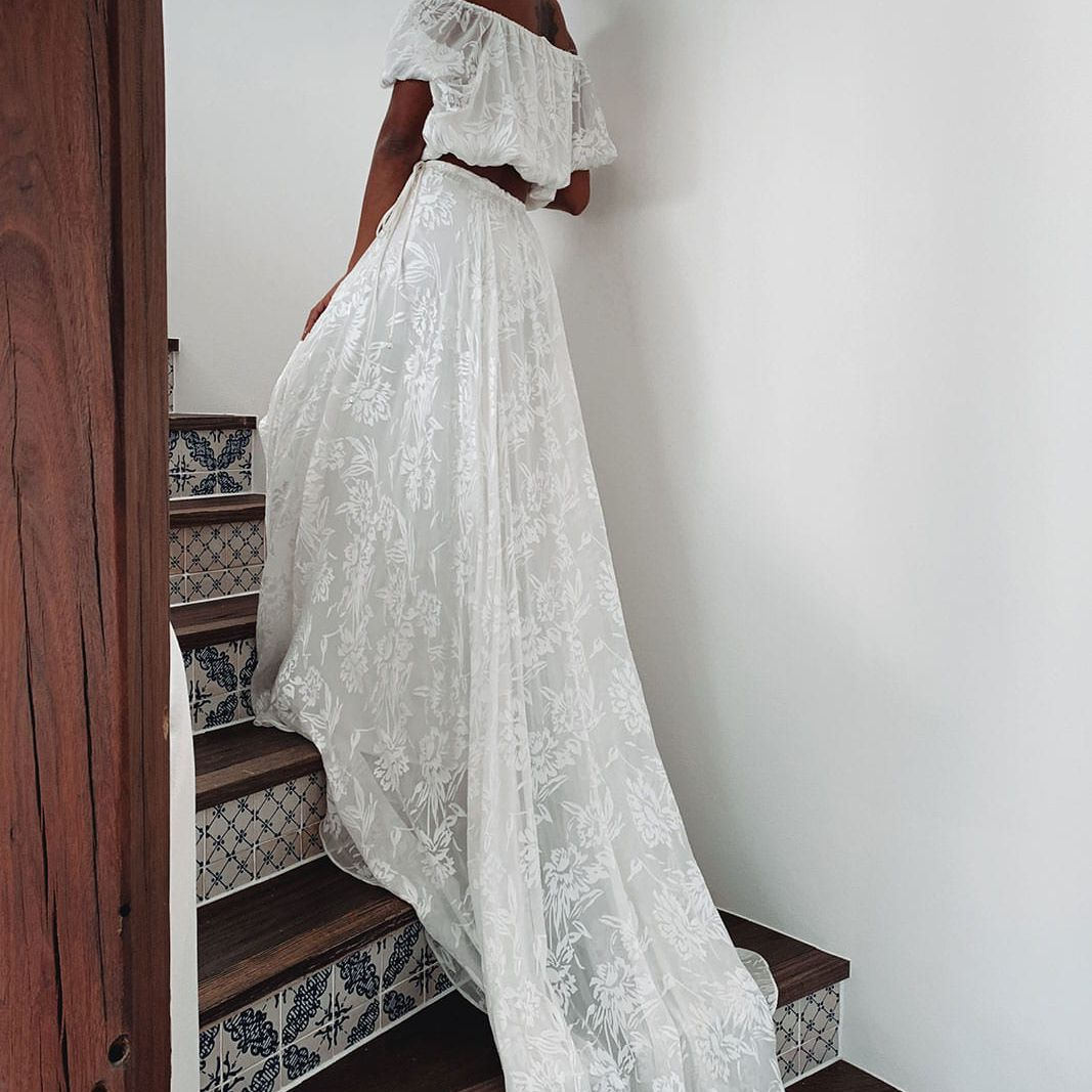 Model walking up stairs in two-piece sheer lace wedding outfit with off-the-shoulder crop top