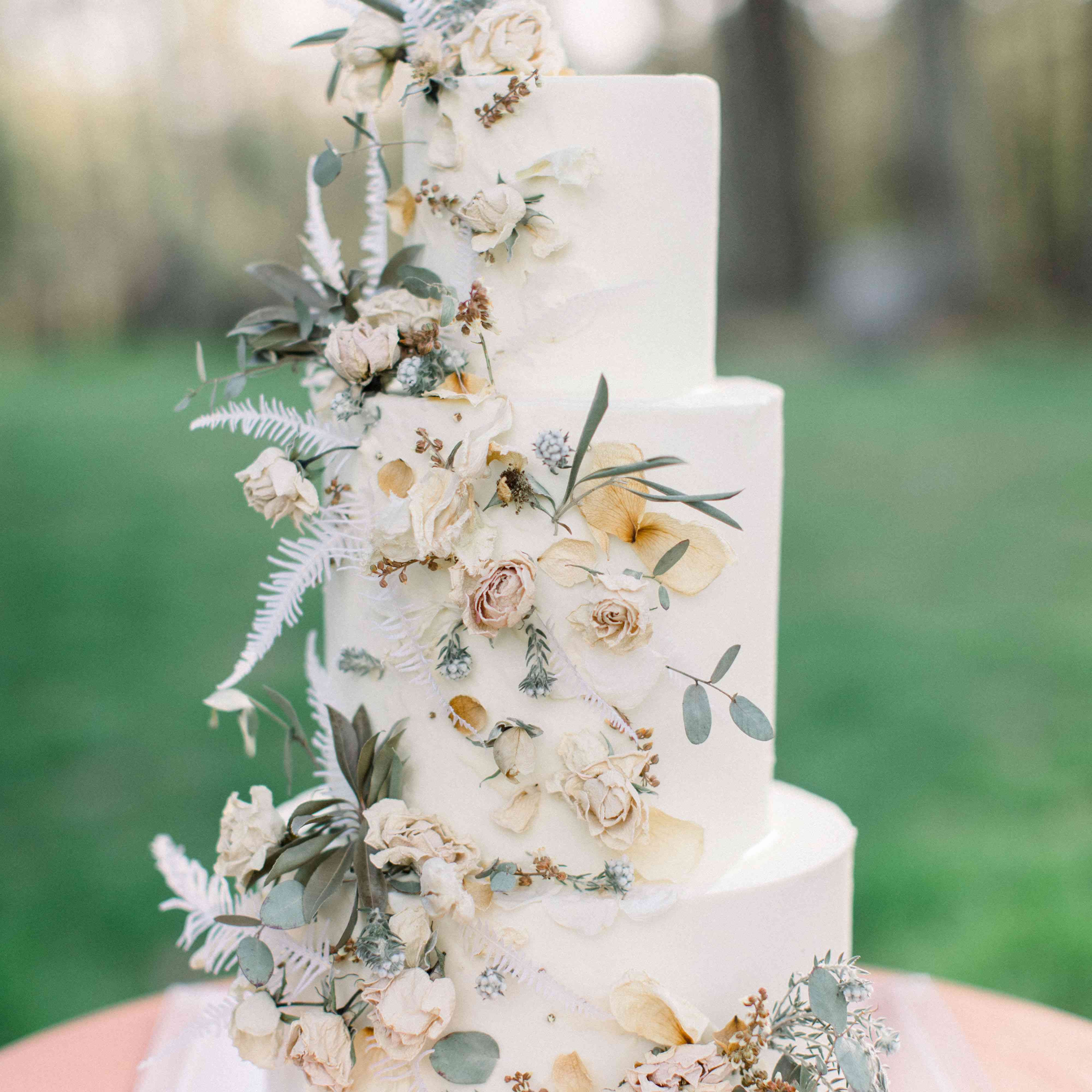 Tiered white wedding cake with leaves and dried floral accents