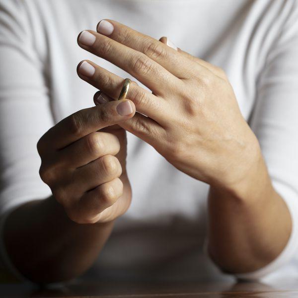 woman taking off wedding ring