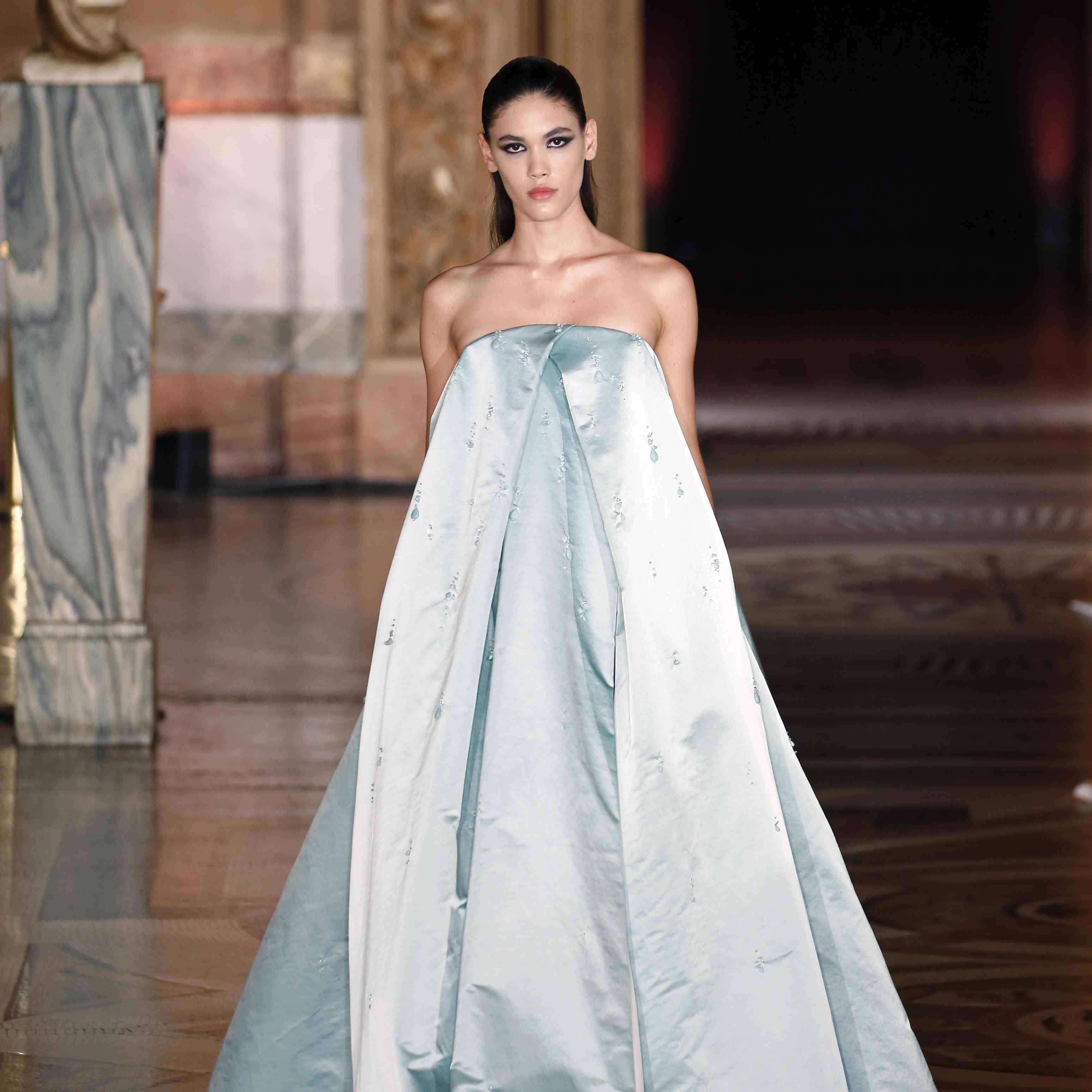 A model walks the runway in light blue, strapless, satin gown