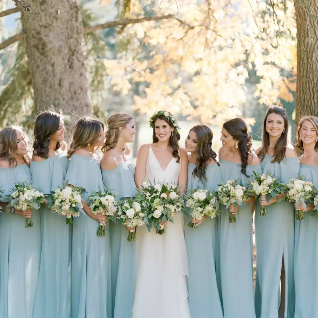 Baby blue bridal party with bride in autumnal forest setting