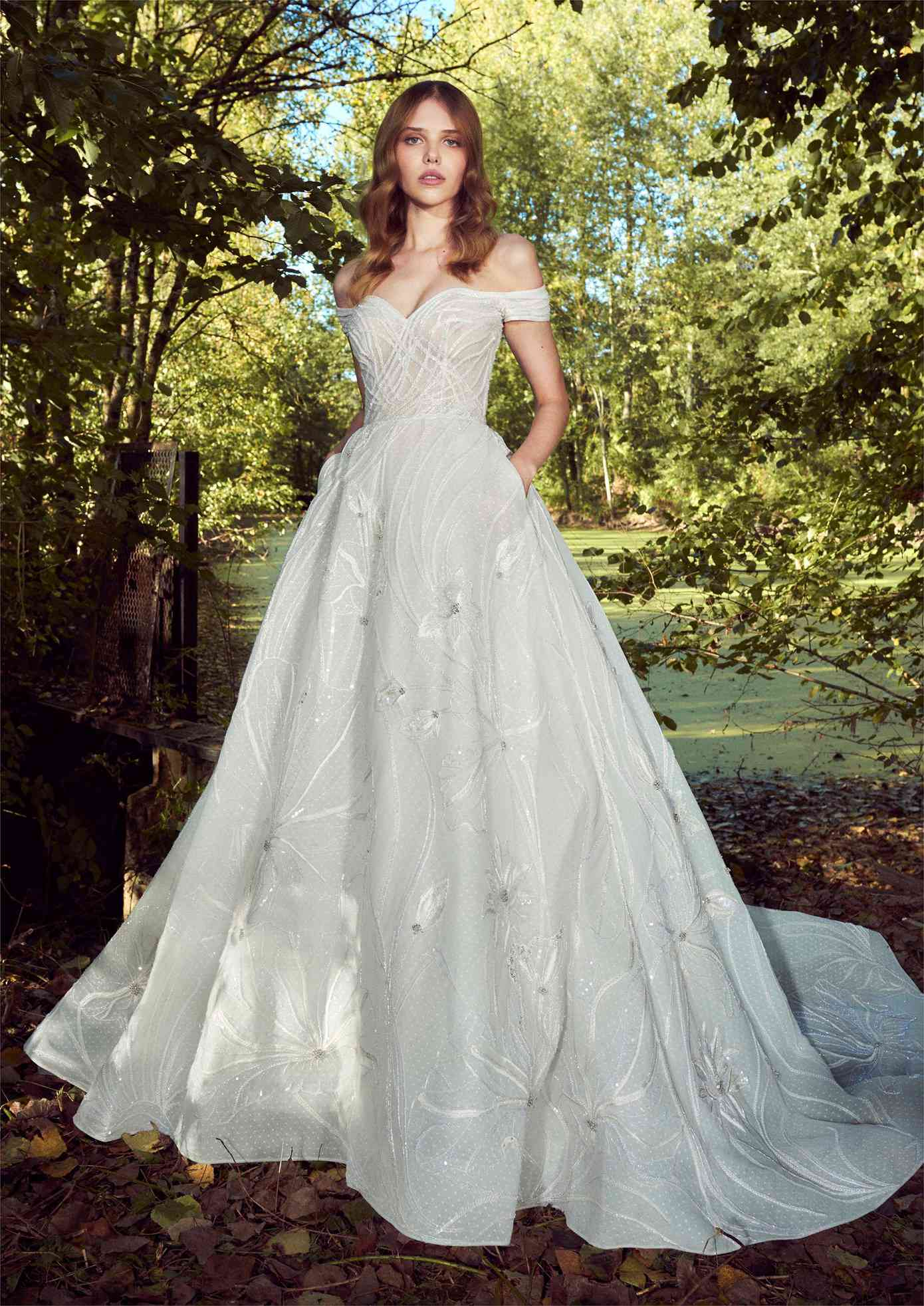 Model in off-the-shoulder sweetheart dotted tulle ballgown with silver beaded embroidery and skirt pockets
