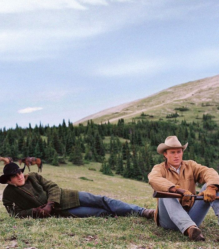 Jake Gyllenhaal and Heath Ledger sitting on a hill in Brokeback Mountain