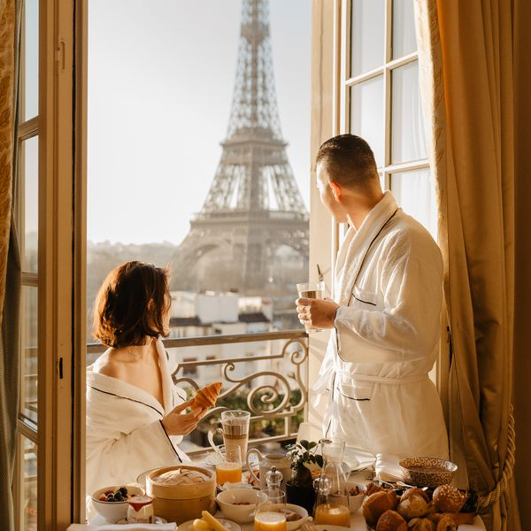 Couple eating breakfast in hotel looking through open patio doors at the Eiffel Tower