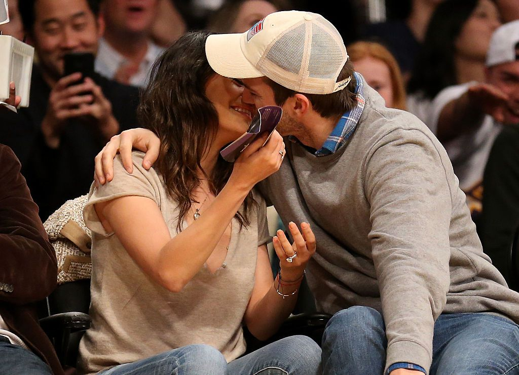 Actors Ashton Kucher and Mila Kunis kiss as they are shown on the video board during the