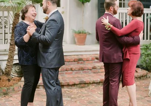 Two grooms dancing with their mothers at their wedding