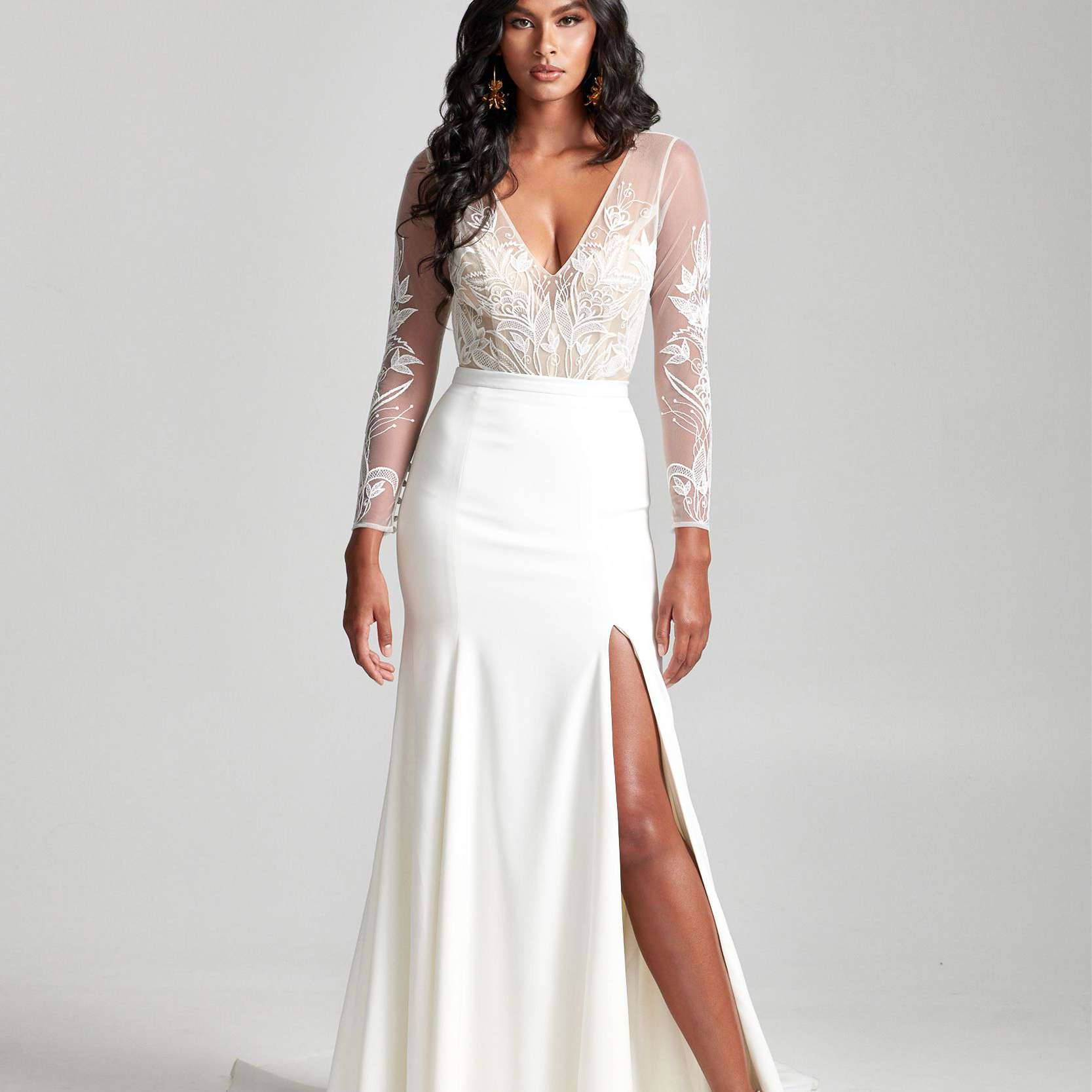 Model in lace v-neck long-sleeve top and skirt with side slit