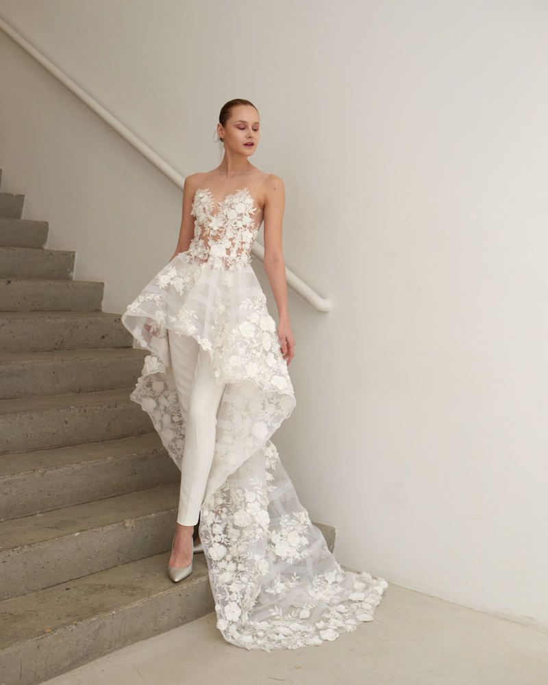 Model in floral white jumpsuit with overskirt
